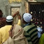 Delhi, Nizamuddin Dargah, proba magicznego przyczepienia monety do sciany